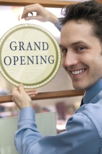 "Picture of a man next to a sign that says ""grand opening"""
