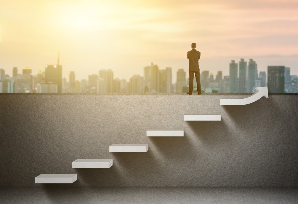 Continuous Improvement. An image of stairs moving upwards with a man standing on a wall near the stairs and overlooking a city scene.